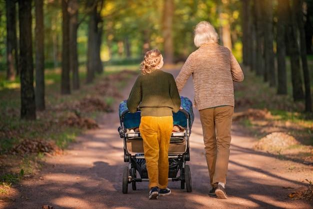 Ouders met een kinderwagen voor een tweeling in park