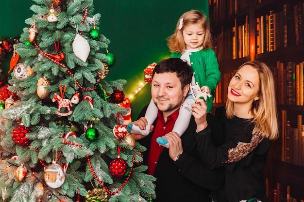 Ouders met een klein blond meisje poseren voor een kerstboom in de kamer