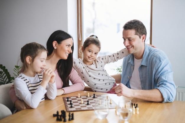 Ouders met gelukkige kleine meisjes binnenshuis, die bordspellen spelen.