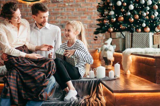 Ouders met hun jonge kinderen zitten in de voor kerstmis versierde woonkamer