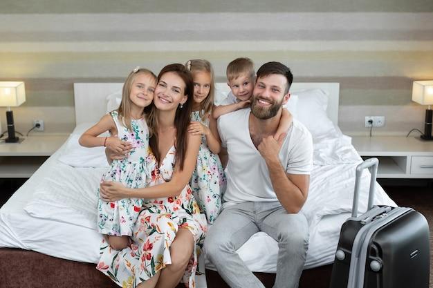 Ouders met kinderen zitten in het hotel op het bed en lachen