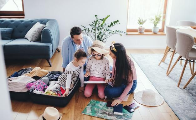Ouders met kleine dochters binnenshuis, nemen selfie bij het inpakken voor de zomervakantie.