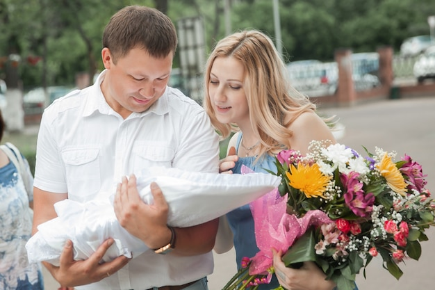 Ouders met pasgeboren baby die zich op stadsstraat bevinden