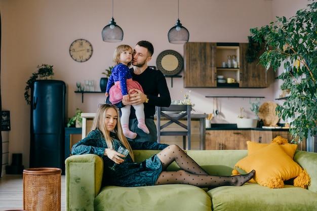 Ouders met plezier met hun dochtertje in interieur studio