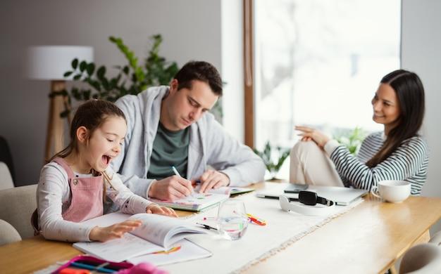 Ouders met schoolmeisje binnenshuis, afstandsonderwijs en thuiskantoorconcept.