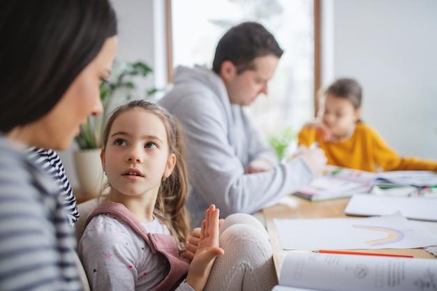 Ouders met schoolmeisjesdochters binnenshuis, afstandsonderwijs.