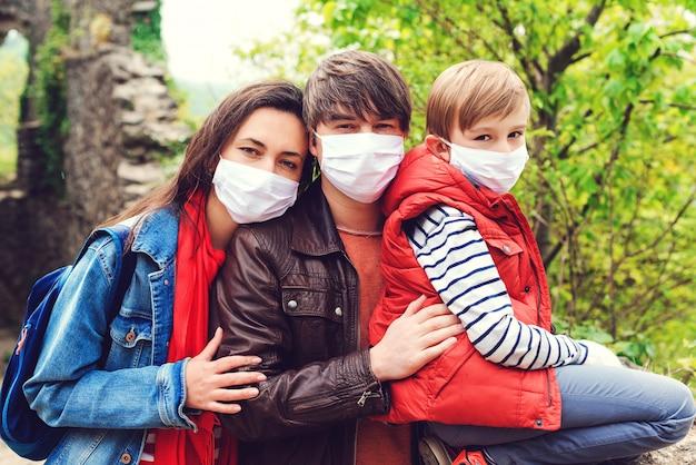 Ouders met zoon die gezichtsmaskers in openlucht dragen. familie samen poseren