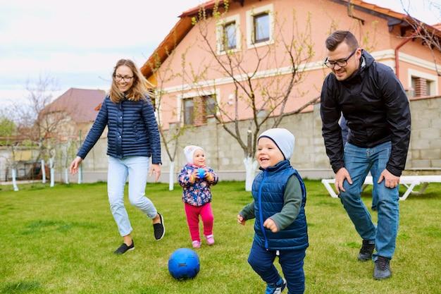 Ouders moeder vader en zoon spelen in de tuin van huis op gr