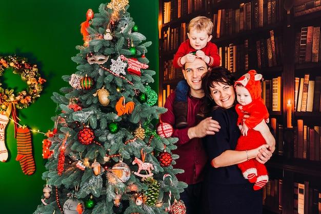 Ouders poseren met hun kleine zonen voor een kerstboom