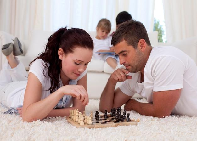 Ouders schaken op de vloer in de woonkamer