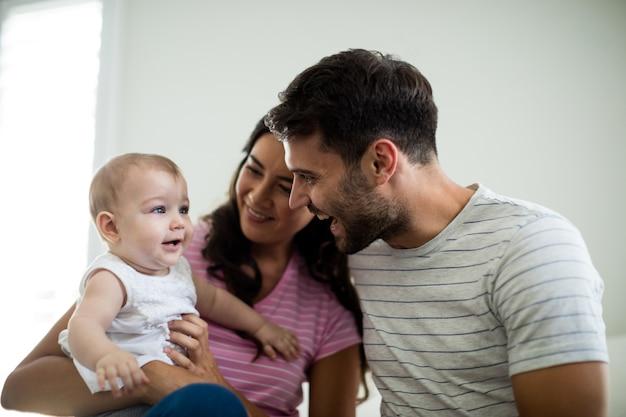 Ouders spelen met hun babymeisje in de slaapkamer thuis