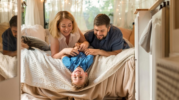 Ouders spelen met hun zoon in het bed van een caravan