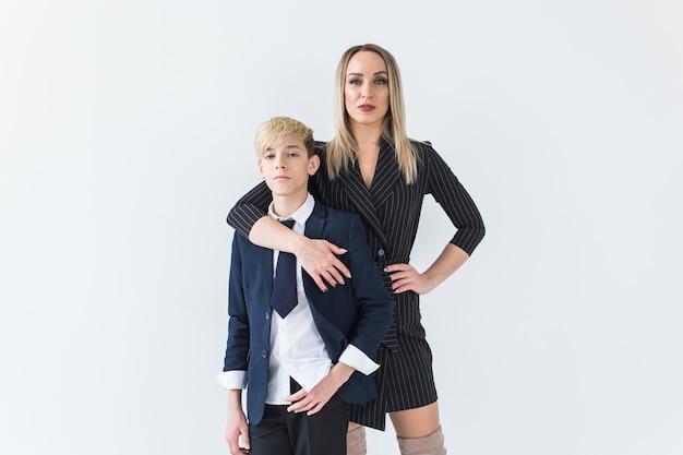 Ouderschap, gezin en alleenstaande ouder concept - een gelukkige moeder en tiener zoon lachend op wit