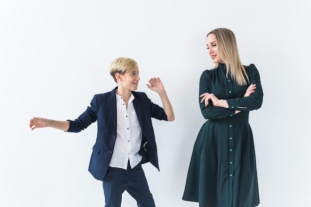 Ouderschap, gezin en alleenstaande ouder concept - een gelukkige moeder en tienerzoon dansen op wit