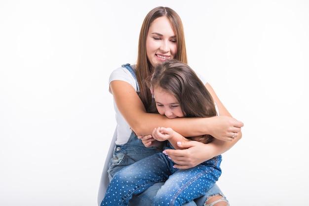 Ouderschap, gezin en kinderen concept - een portret van een moeder en haar babymeisje hebben plezier en glimlachen over een witte muur.