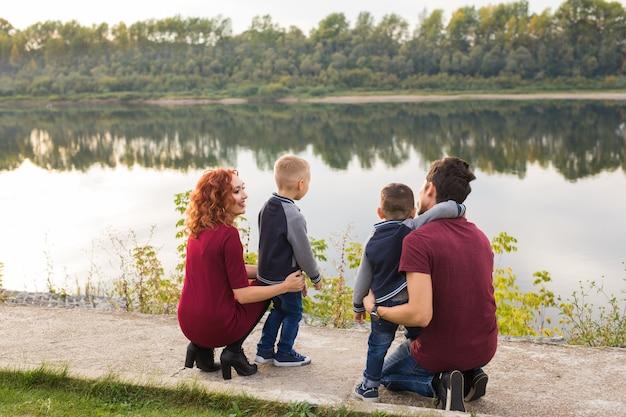 Ouderschap jeugd en familie concept ouders en twee mannelijke kinderen wandelen in het park en