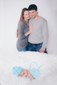 Ouderschap, kinderdag, medicijnen, ivf-vader en moeder kijken naar de slapende pasgeborene en aaien het. geïsoleerd op witte achtergrond