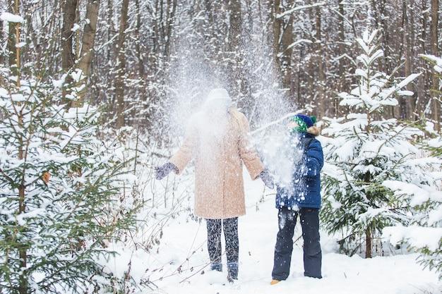 Ouderschap, plezier en seizoensconcept - gelukkige moeder en zoon die plezier hebben en spelen met sneeuw in het winterbos.
