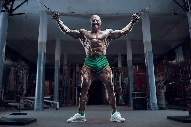 Ouderwetse atleet bodybuilder arm oefeningen doen in de sportschool. brute kale kaukasische sportman stijl van de jaren 80. sport, fitness en workout 80's concept