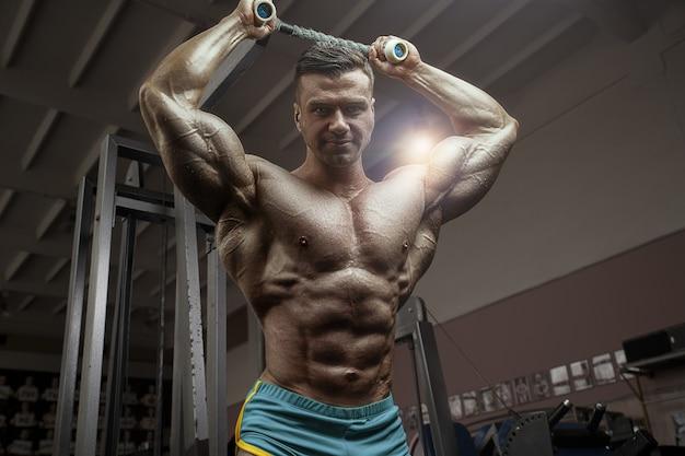 Ouderwetse bodybuilder die armoefeningen doet in de sportschool. knappe kaukasische sportman stijl van de jaren 80. sport, fitness en workout 80's concept