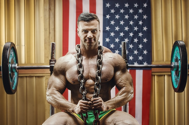Ouderwetse bodybuilder die oefeningen doet in de sportschool van de oude school met amerikaanse vlag. knappe kaukasische sportman stijl van de jaren 80. sport, fitness en workout 80's concept