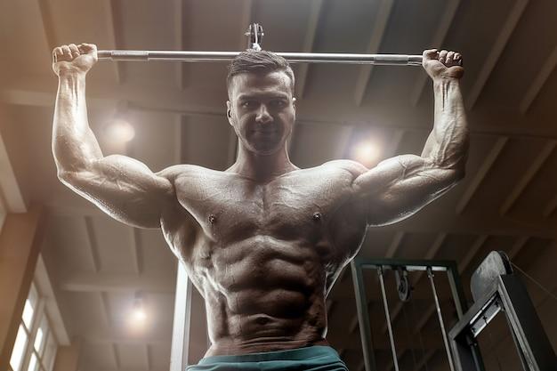 Ouderwetse bodybuilder die optrekoefeningen doet in de sportschool. knappe kaukasische sportman stijl van de jaren 80. sport, fitness en workout 80's concept