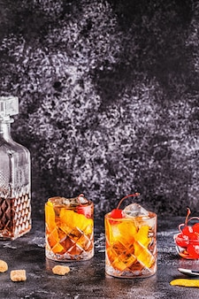 Ouderwetse cocktail met kersen en oranje twist, selectieve aandacht.