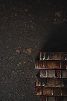 Ouderwetse flat lag met stapel antieke leergebonden boeken tegen een donkere muur