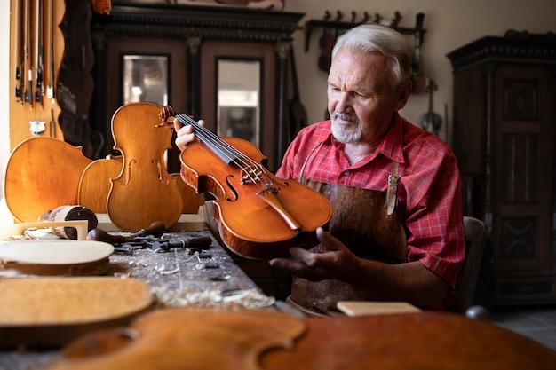 Ouderwetse houtbewerker die zijn meesterwerk vasthoudt en bewondert