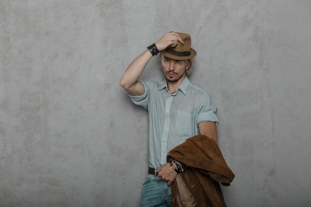 Ouderwetse jongeman hipster met een baard met bruin jasje in een klassiek shirt in spijkerbroek