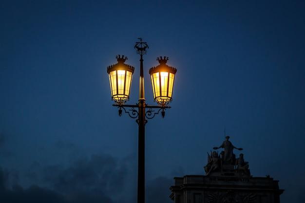 Ouderwetse straatlantaarn 's nachts. magische lamp met een warm geel licht in de schemering van de stad.