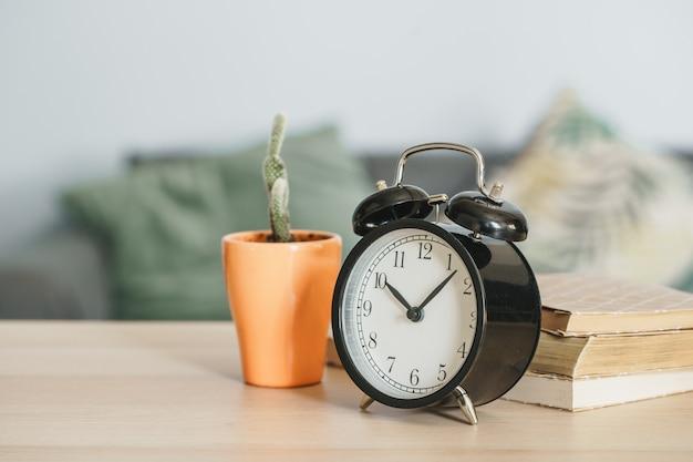 Ouderwetse wekker en kamerplant op houten tafel