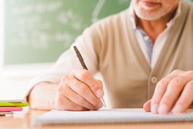 Ouderwetse wiskundeleraar die bij voorbeeldenboek schrijven