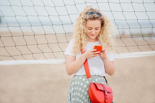Oudoor shot van prettig uitziende blonde vrouw houdt mobiele telefoon, deelt foto's in sociale netwerken.