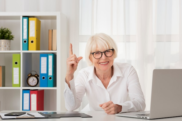 Oudste die met oogglazen in haar bureau zit