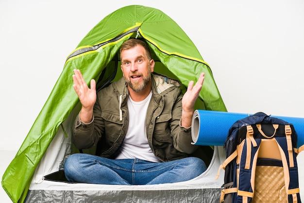 Oudste in een tent die op wit wordt geïsoleerd dat een aangename opgewonden verrassing ontvangt en handen opheft.