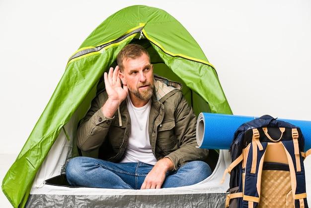 Oudste in een tent die op witte achtergrond wordt geïsoleerd die probeert om een roddel te luisteren.