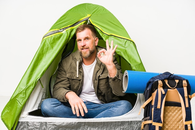 Oudste in een tent die op witte ruimte wordt geïsoleerd vrolijk en zeker die ok gebaar toont.