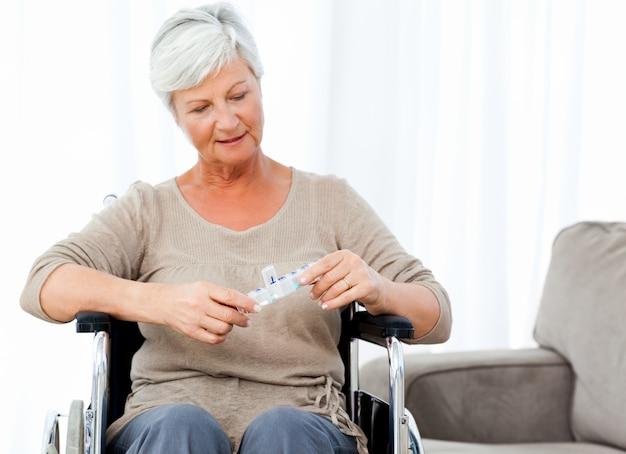 Oudste in rolstoel met pillen