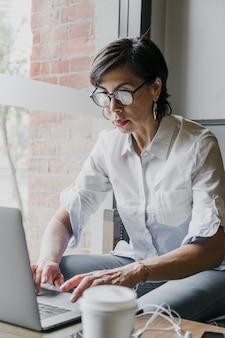 Oudste met oogglazen die aan laptop werken