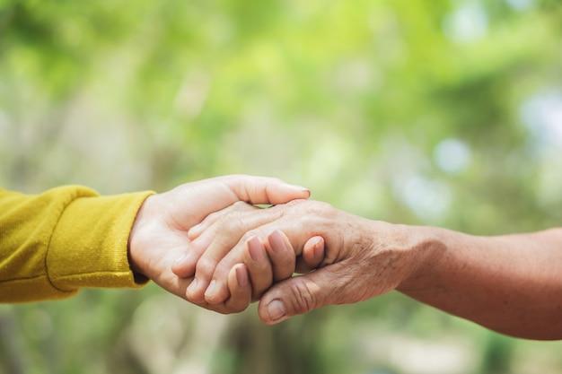 Oung en oude vrouwenhand die elkaar houden