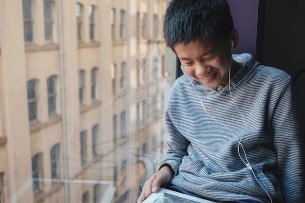 Oung mengde aziatisch preteen jongen thuis gebruikend digitale tablet