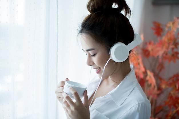 Oung mooie vrouw die in heldere uitrusting van de muziek thuis geniet