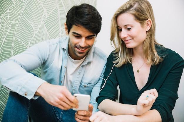 Ouple delen van koptelefoon kijken naar smartphone
