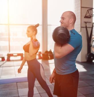 Ð¡ouple functionele training. sportieve man en fit vrouw doen oefening met kettlebell in sportschool