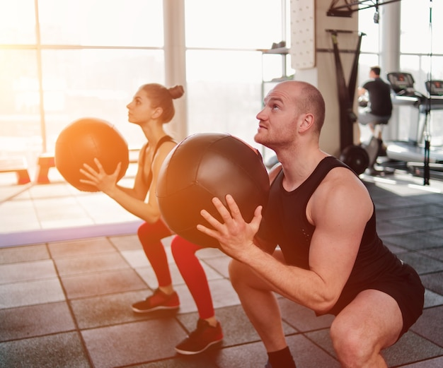 Ð¡ouple functionele training. sportieve man en fitte vrouw oefenen met medicijnbal in de sportschool