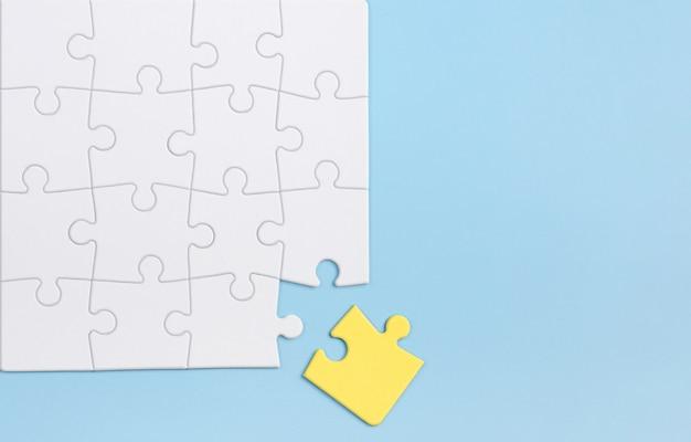 Out of the box denken en individualiteit concept. gele puzzel tegen witte degenen op blauwe muur.