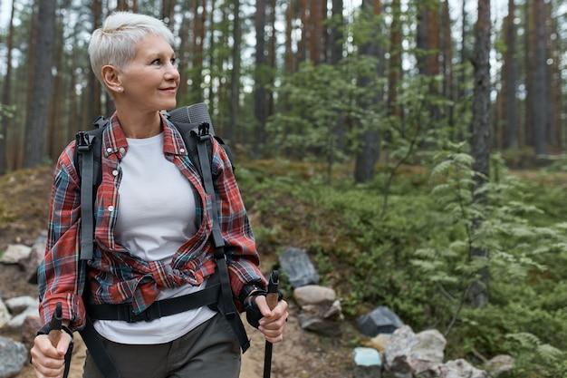 Outddor portret van gelukkige europese vrouwelijke gepensioneerde m / v met rugzak en stokken, genieten van de prachtige natuur tijdens nordic walking in dennenbos.