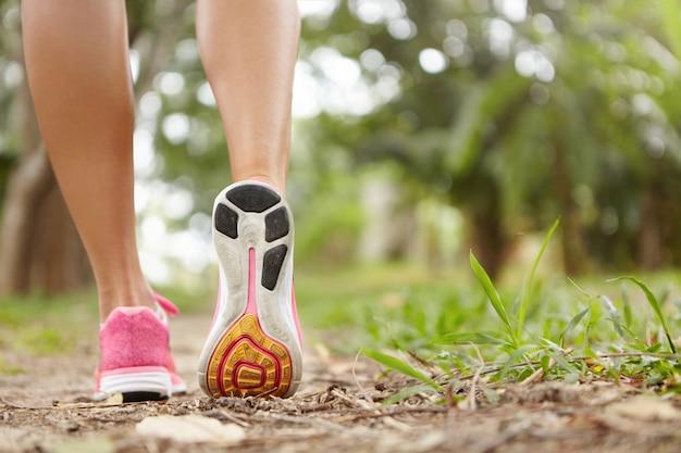 Outdoor-activiteit en sport. bevriezen actie close-up van roze loopschoenen tegen groen gras. vrouw jogger oefenen in park of bos, voorbereid op marathon.