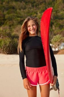 Outdoor activiteiten concept. foto van tevreden, goed uitziende vrouw draagt een boardshort, heeft slanke benen, een gebruinde huid, beschermt het gezicht met een zinkmasker